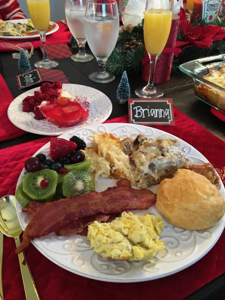 christmas brunch table scape with bacon eggs rolls sausage breakfast strata kiwis and berries Bavarian lemon ice mimosas and chalk name tags on a white plate and red velvet placemats and miniature christmas trees