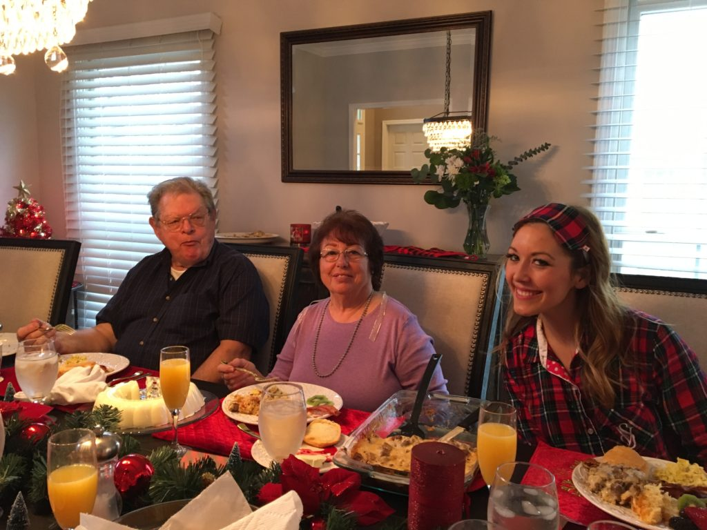 Brianna K with GG and Papa on Christmas morning 2017 eating brunch in the dining room- lemon Bavarian ice with raspberries, eggs, bacon, sausage breakfast casserole strata, and mimosas