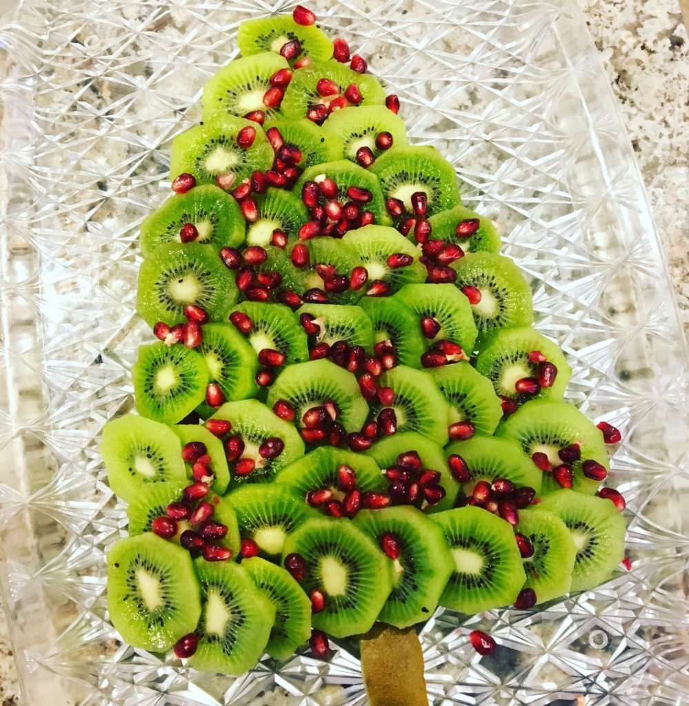 Christmas tree made out of kiwi slices and pomegranate seeds for Christmas Day brunch