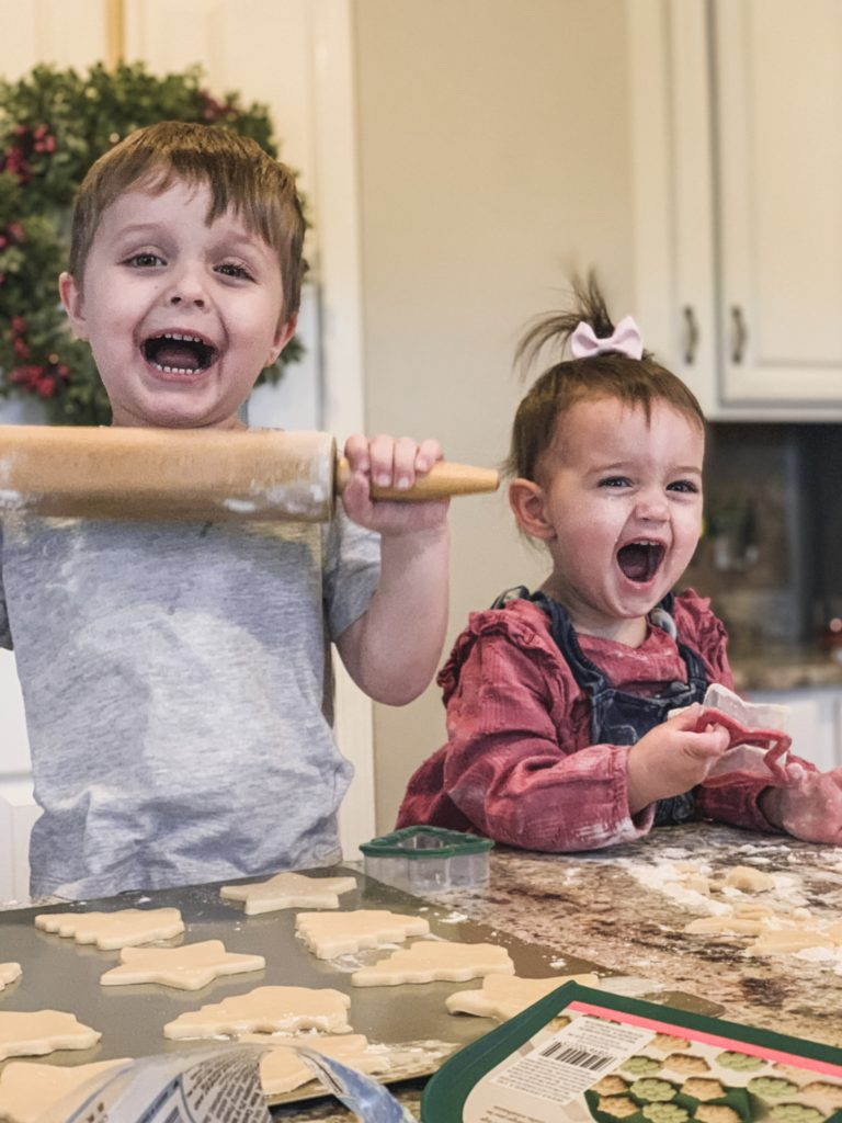 boy Landon and girl Presley smiling baking cutout christmas cookies with rolling pin and cookie cutters in the shapes of stars christmas trees and gingerbread men with flour all over. Brianna k's kids Landon and Presley baking cookies for christmas 2018.