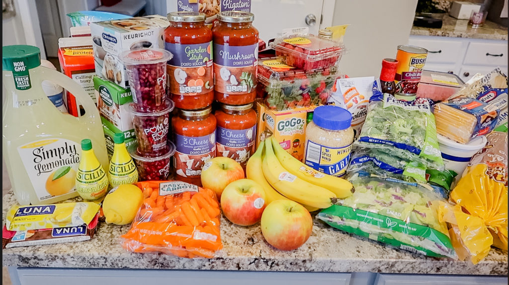 grocery haul of bananas apples salad broccoli pasta tomato sauce coffee lemons lemonade carrots salad pomegranates macaroni and cheese bread for meal planning for one week breakfast lunch and dinner for a family of four on a budget of $200