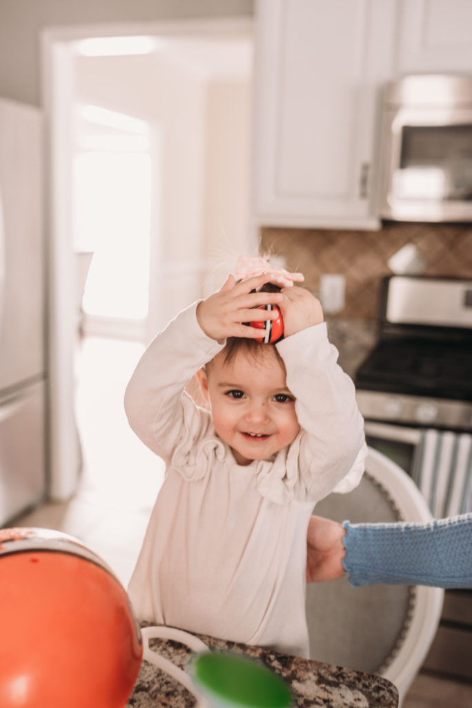 Presley putting on a toy football helmet that was a decoration for super bowl party prep with febreze