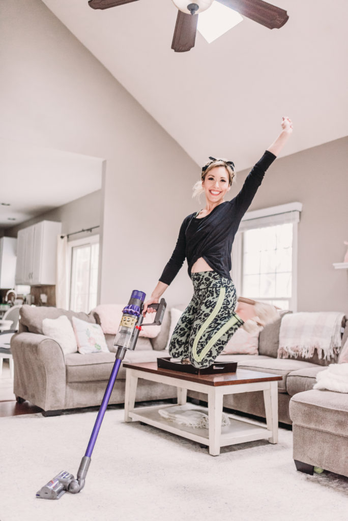 Brianna K bitsofbri cleaning her family room with a purple Dyson vacuum while jumping up and down with joy because she loves to clean her home