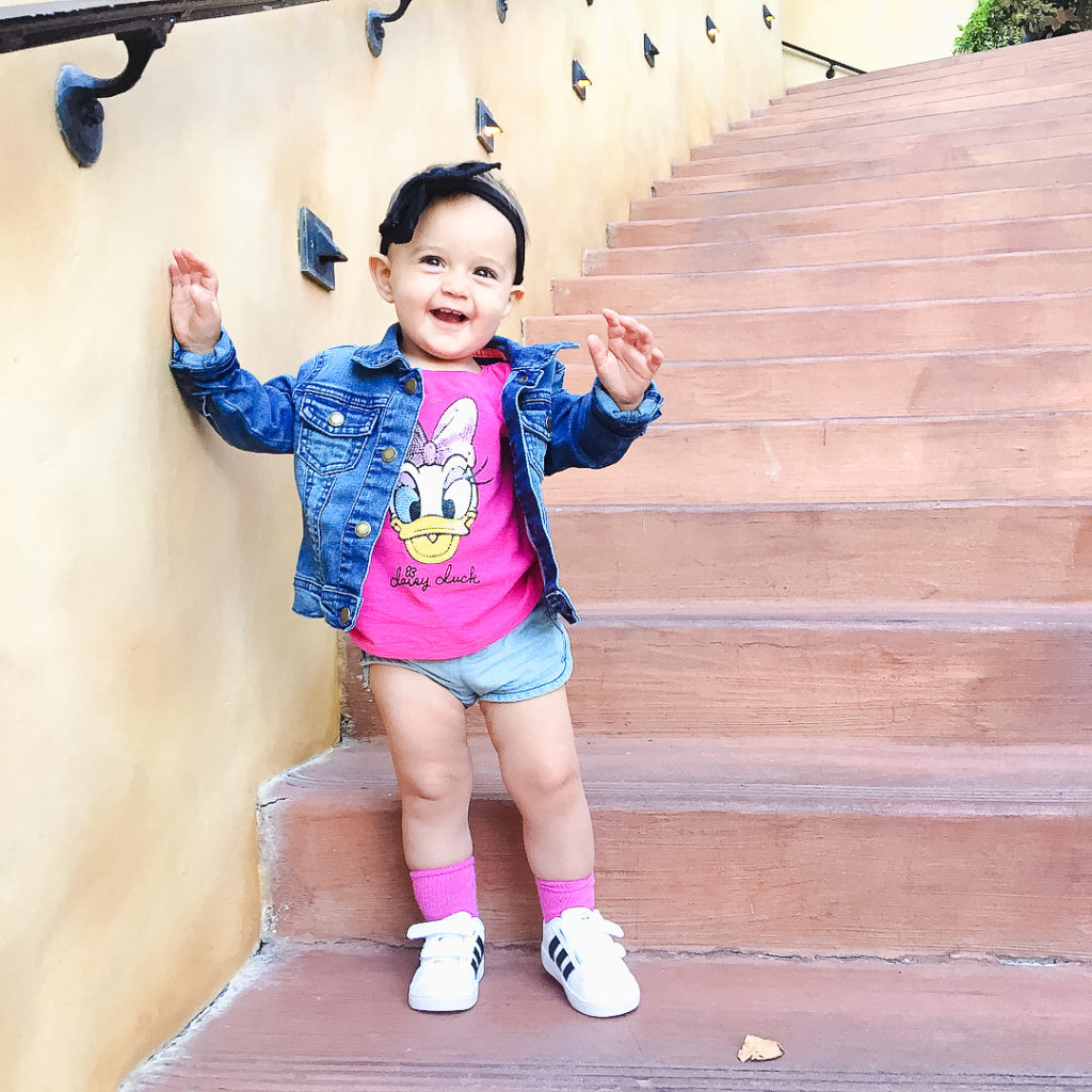 Presley on the steps at Wine Country Trattoria at Disney's California Adventure Park, one of our favorite restaurants because it feels like you're outside at a Tuscan Winery! Disneyland vacation planning tips and tricks from a Disney Pro. Brianna K Bitsofbri bits of bri Cleveland mom blog Disneyland planning advice where to stay what to eat what age to go to disney
