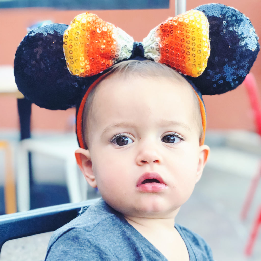 Presley wearing candy corn Mickey ears for Halloween. They put up Halloween decor our last day at Disneyland when we went the first week of September. Disneyland vacation planning tips and tricks from a Disney Pro. Brianna K Bitsofbri bits of bri Cleveland mom blog Disneyland planning advice where to stay what to eat what age to go to disney