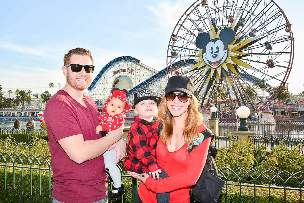 Family pic in front of the Pixar-Pal-Around Ferris wheel  at Disney's California Adventure park in December 2017. Landon was 2 1/2 and Presley was 7 months old. Disneyland vacation planning tips and tricks from a Disney Pro. Brianna K Bitsofbri bits of bri Cleveland mom blog Disneyland planning advice where to stay what to eat what age to go to disney