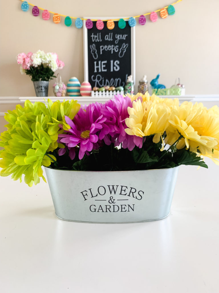 green purple and yellow dollar tree DIY flower decor in silver pot with easter decoration in the background  Brianna K bits of bri bitsofbri easter decor house tour 2019 spring and easter decorations around her home flowers bunnies dollar tree DIY decorations