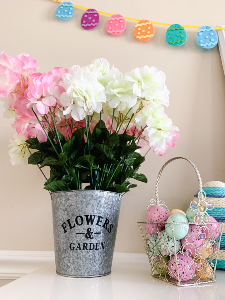 pink and white hydrangea in silver pot dollar tree DIY craft surrounded by easter basket with Easter eggs  Brianna K bits of bri bitsofbri easter decor house tour 2019 spring and easter decorations around her home flowers bunnies dollar tree DIY decorations