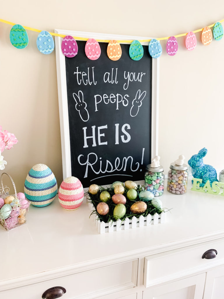 easter decorations surrounding chalk board sign that says tell all your peeps he is risen  Brianna K bits of bri bitsofbri easter decor hour tour 2019 spring and easter decorations around her home flowers bunnies dollar tree DIY decorations