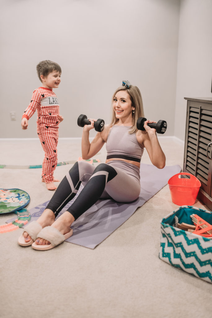 Brianna K works out in basement playroom lifting weights on exercise mat while son Landon puts a toy race car on her head. Fitness routine for busy moms tips how to advice for mommy Brianna K bitsofbri blog post staying in shape after baby how to lose baby weight