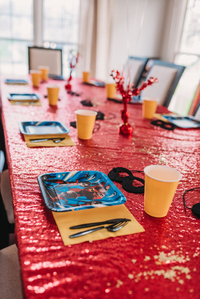 REd glitter table cloth, incredibles plates, yellow napkins and cups, black utensils, black super hero masks, gold confetti, and gold, black and red star balloons from the dollar tree to decorate for landon's 4th birthday party HOW TO PLAN AN INCREDIBLE BIRTHDAY PARTY | BE YOUR OWN PARTY PLANNER CHECKLIST! Brianna K bitsofbri blog