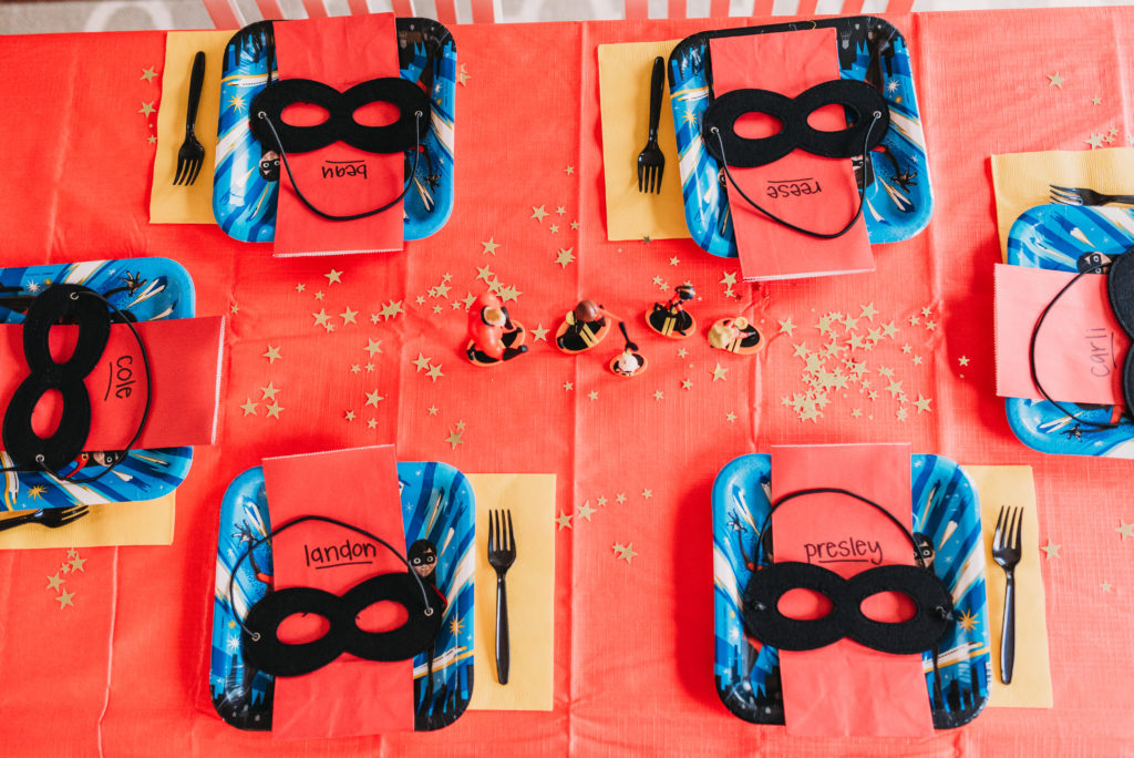 tablescape for incredibles birthday party with plates, super hero black masks, red goodie bags with personalized name, incredibles plates, yellow napkins, black utensils, gold star confetti and incredibles figurines of mr. incredible, elastigirl, violet, dash, and jack jack HOW TO PLAN AN INCREDIBLE BIRTHDAY PARTY | BE YOUR OWN PARTY PLANNER CHECKLIST! Brianna K bitsofbri
