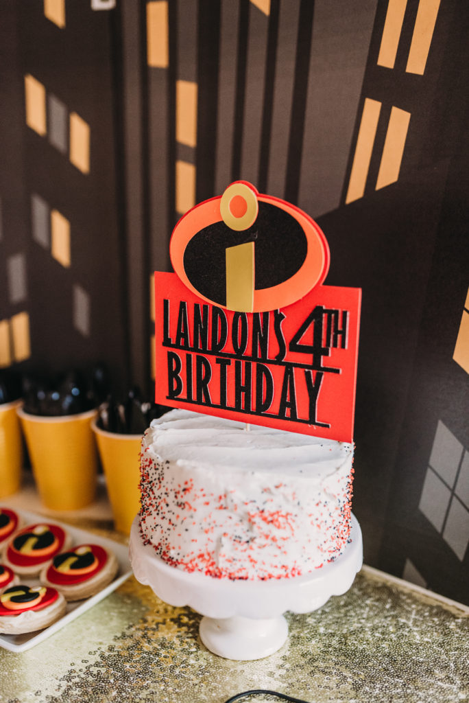 "frosted white birthday cake with personalized incredibles sign that says ""landon's 4th birthday"" HOW TO PLAN AN INCREDIBLE BIRTHDAY PARTY 