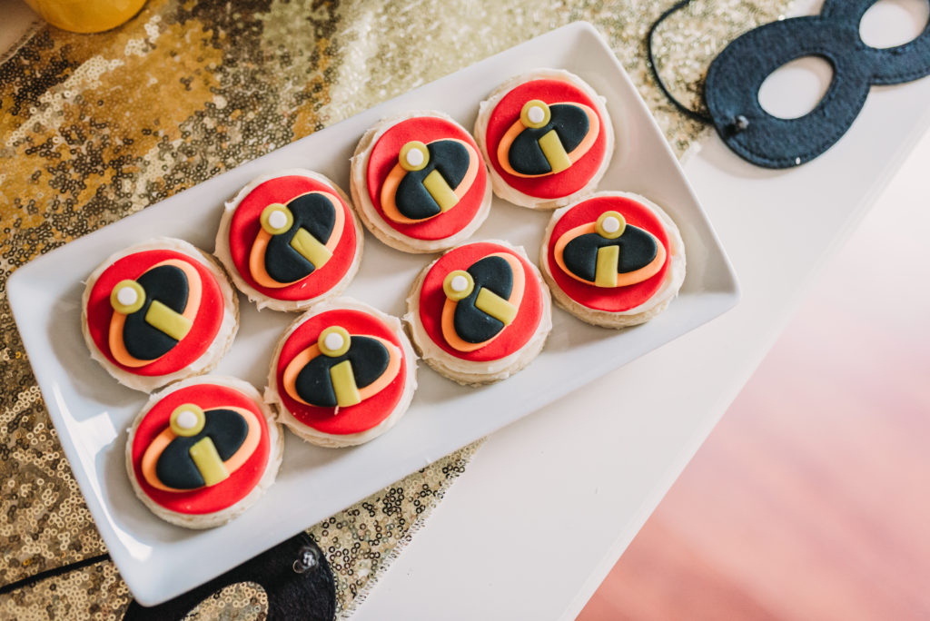 incredibles logo fondant cookie toppers on top of homemade butter cookies HOW TO PLAN AN INCREDIBLE BIRTHDAY PARTY | BE YOUR OWN PARTY PLANNER CHECKLIST! Brianna K bitsofbri