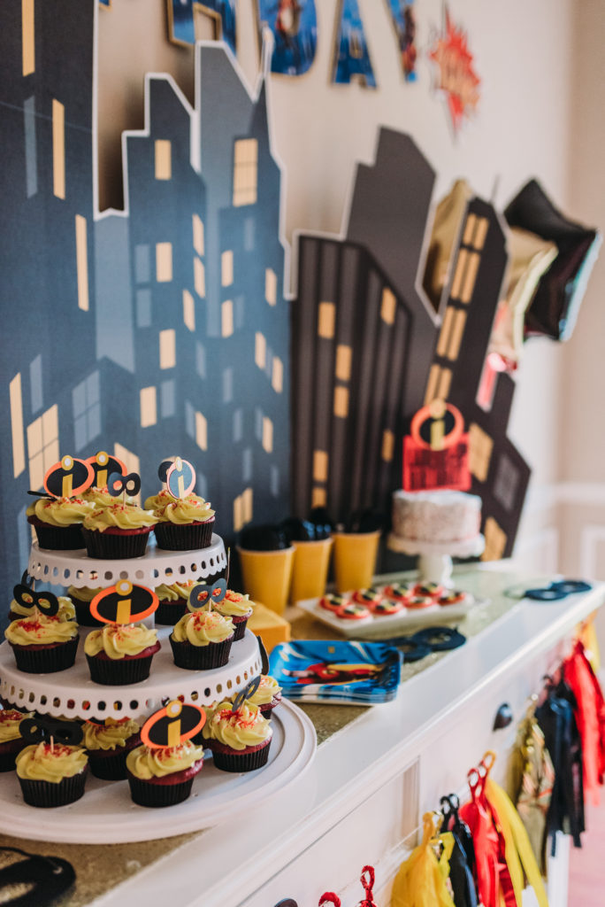 dessert table at incredibles birthday party with cupcakes with black cupcake holder, red velvet cake, yellow frosting and incredibles cupcake toppers with black masks and incredibles logo HOW TO PLAN AN INCREDIBLE BIRTHDAY PARTY | BE YOUR OWN PARTY PLANNER CHECKLIST! Brianna K bitsofbri