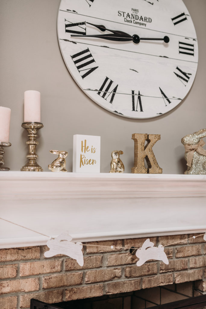 mantle decorated for easter with pink candles gold easter bunnies and white bunny garland  Brianna K bits of bri bitsofbri easter decor house tour 2019 spring and easter decorations around her home flowers bunnies dollar tree DIY decorations