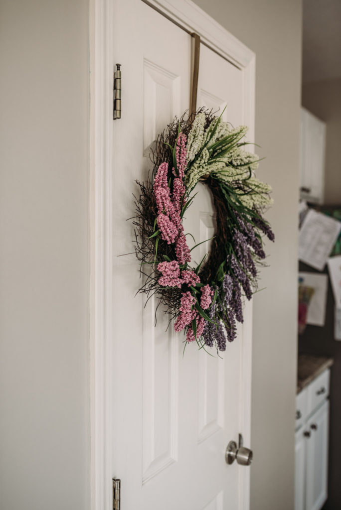 purple mauve and white flower wreath in kitchen hanging on pantry door  Brianna K bits of bri bitsofbri easter decor house tour 2019 spring and easter decorations around her home flowers bunnies dollar tree DIY decorations