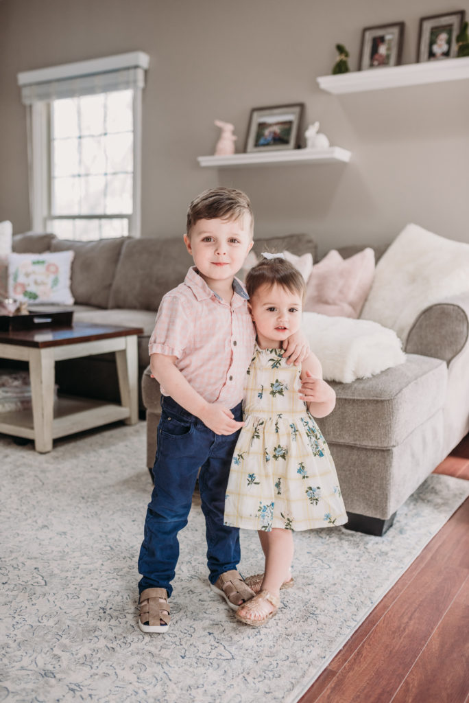 Landon and Presley cuddling in their easter outfits in the family room decorated for easter with pink and mauve pillows and easter bunnies  Brianna K bits of bri bitsofbri easter decor house tour 2019 spring and easter decorations around her home flowers bunnies dollar tree DIY decorations