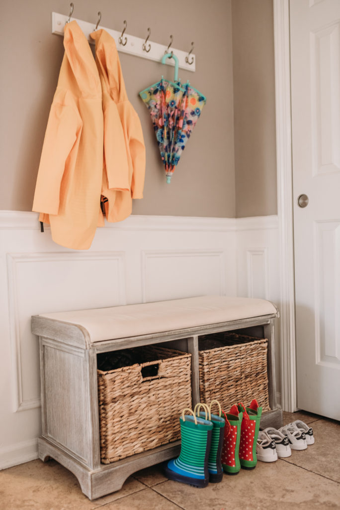 gray foyer bench with white wooden hook yellow rain coats umbrella and rain boots and Adidas sneakers Brianna K house tour foyer  Brianna K bits of bri bitsofbri easter decor hour tour 2019 spring and easter decorations around her home flowers bunnies dollar tree DIY decorations
