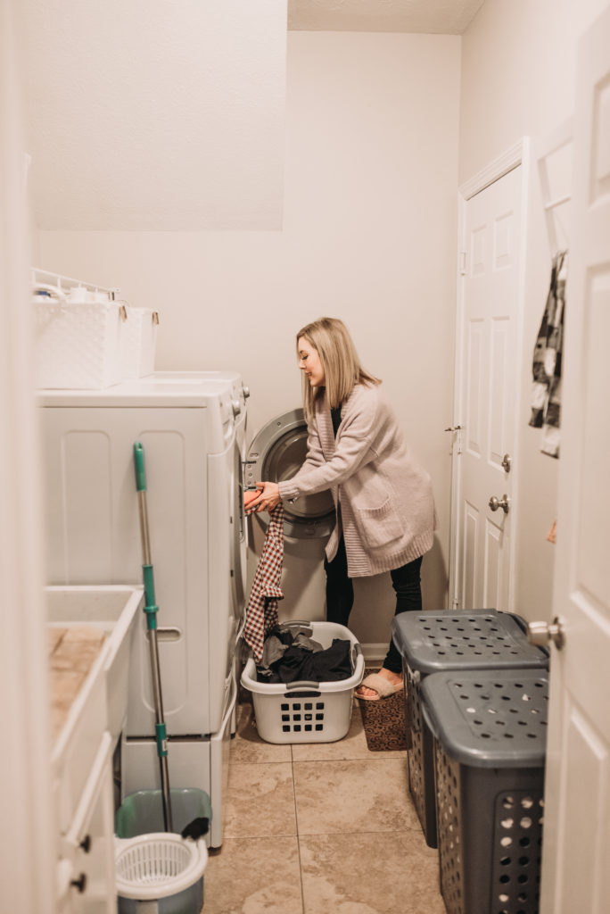 Brianna K in her laundry room taking clothes out of the dryer sharing 5 easy laundry hacks and tips! Bits of Bri blog laundry room tips and tricks