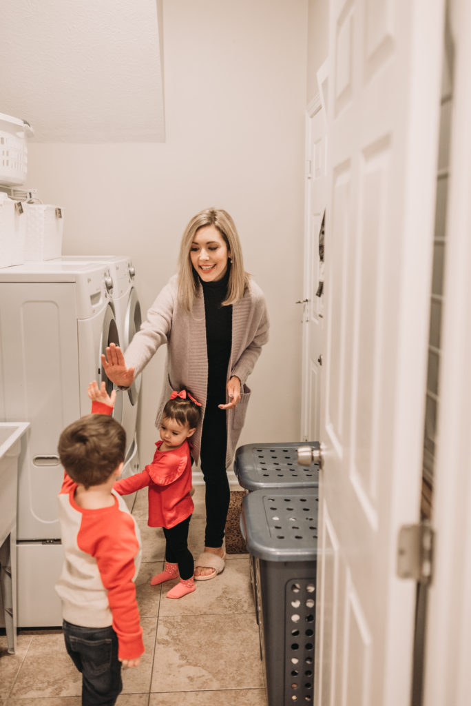 Brianna K in her laundry room with children Landon and Presley giving a high five after sharing 5 easy laundry hacks and tips! Bits of Bri blog laundry room tips and tricks