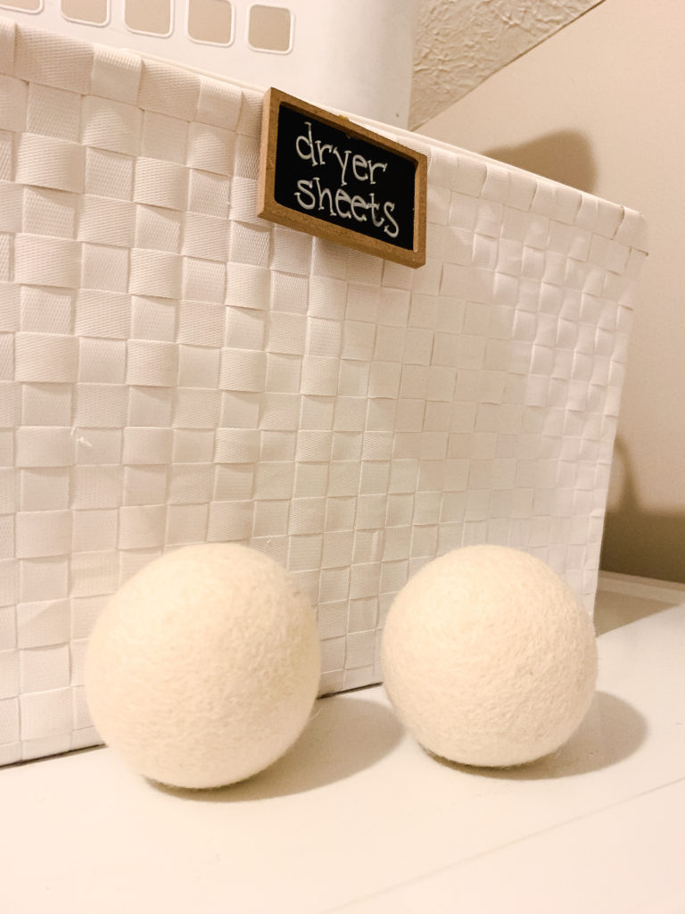 Brianna K dryer balls on top of dryer and dryer sheets bin sharing 5 easy laundry hacks and tips! Bits of Bri blog laundry room tips and tricks