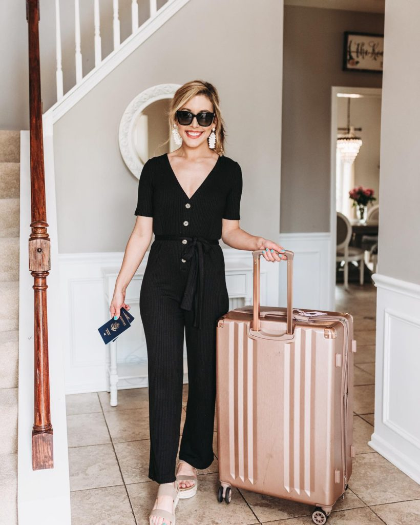Brianna K with rose gold Calpak suitcase and passport in black travel jumpsuit and black sunglasses with white tassel earrings | 10 SUMMER MUST HAVES 2019 BITS OF BRI BLOG BY BRIANNA K