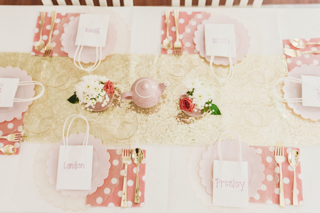 tea party place settings on white table gold, gold glitter table runner, pink polka dot napkins, gold scalloped plate with pink scalloped plate and gold utensils with fresh pink roses and white flowers and baby's breath in the teacup and teapot. TEA FOR TWO   PRESLEY'S SECOND BIRTHDAY DECORATIONS + PARTY IDEAS! Brianna K bitsofbri blog