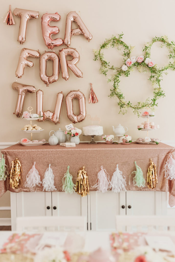 rose gold tea for two balloons and Minnie Mouse ring wreath with tea party decorations of a blush tablecloth and white three tiered stands with bakery and teapots and tea cups and birthday cake TEA FOR TWO | PRESLEY'S SECOND BIRTHDAY DECORATIONS + PARTY IDEAS! Brianna K bitsofbri blog