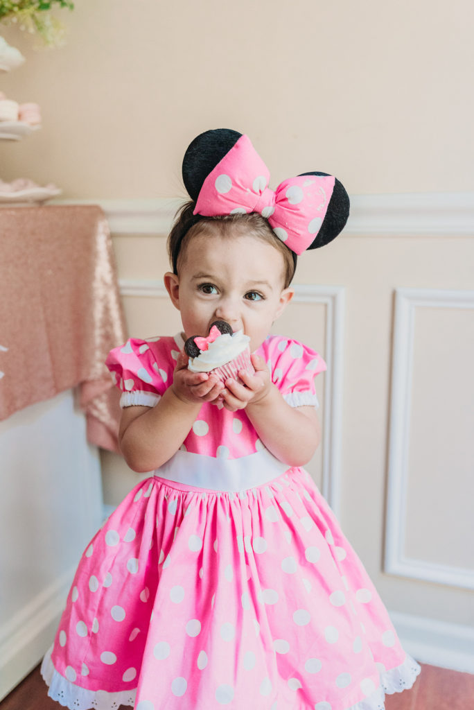 Presley in pink Minnie Mouse polkadot party dress eating a minnie mouse cupcake  for her two year old birthday party TEA FOR TWO   PRESLEY'S SECOND BIRTHDAY DECORATIONS + PARTY IDEAS! Brianna K bitsofbri blog