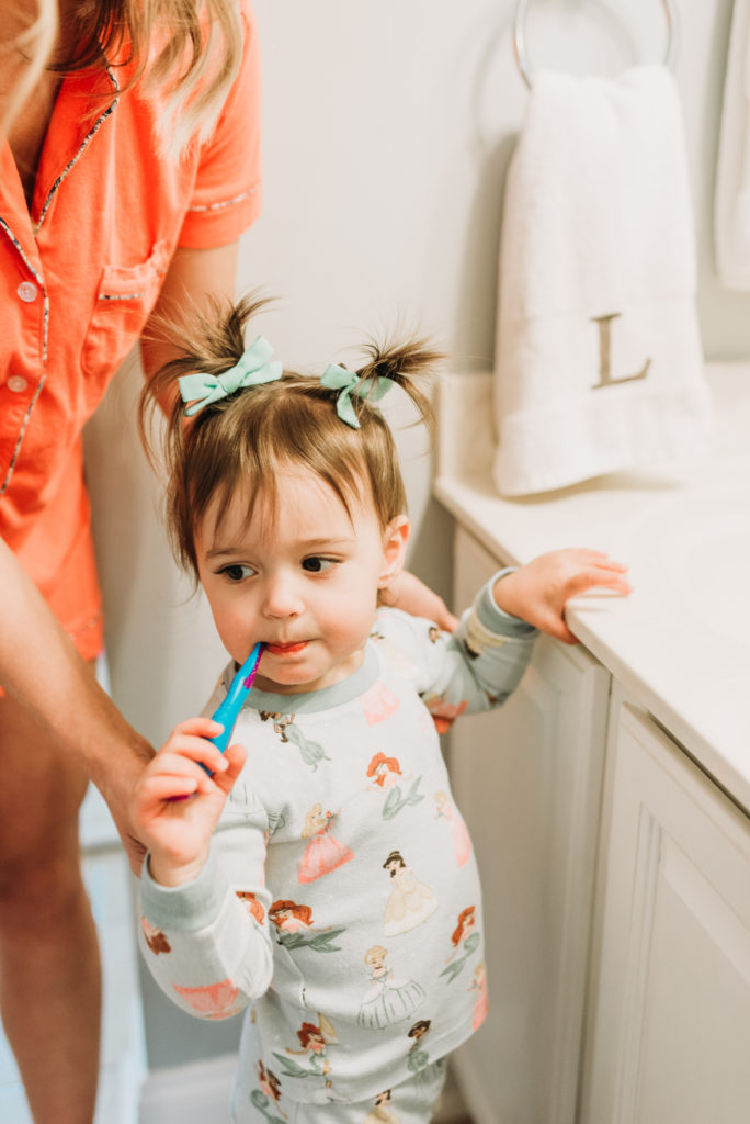Presley toddler girl with pigtails in bathroom brushing her teeth with a toothbrush how to get your toddler to brush their teeth Brianna K bitsofbri