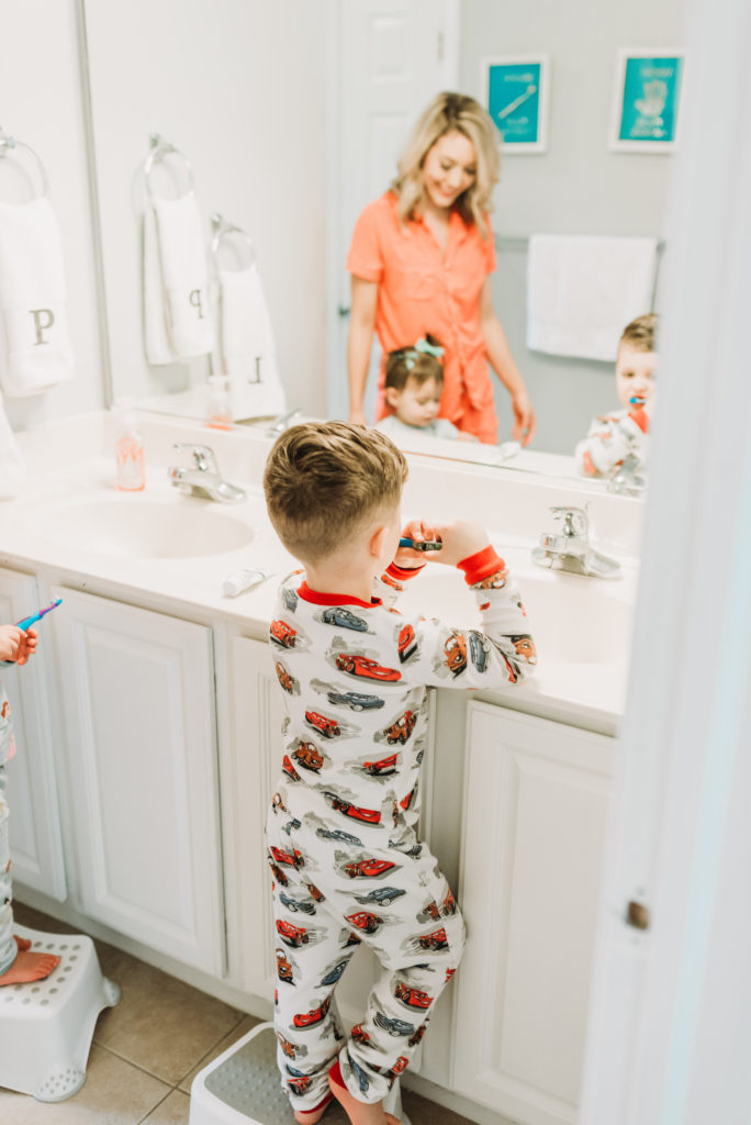 Mom  in bathroom helping her toddlers to brush their teeth with a toothbrush how to get your toddler to brush their teeth Brianna K bitsofbri