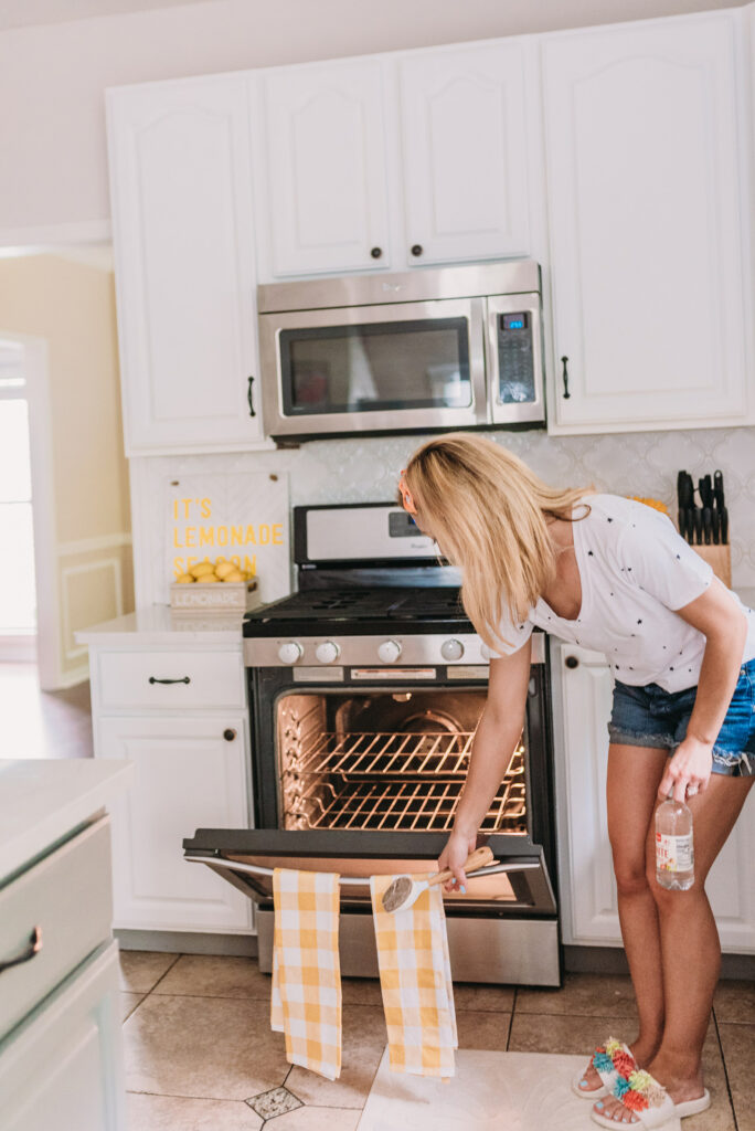 Brianna K wearing white tee shirt with black stars and blue jean cut off shorts with an orange scarf tied around her hair sharing how to clean your stove with natural cleaning products in her new all white kitchen decorated with pops of yellow decor for summer 2019. Bitsofbri Blog