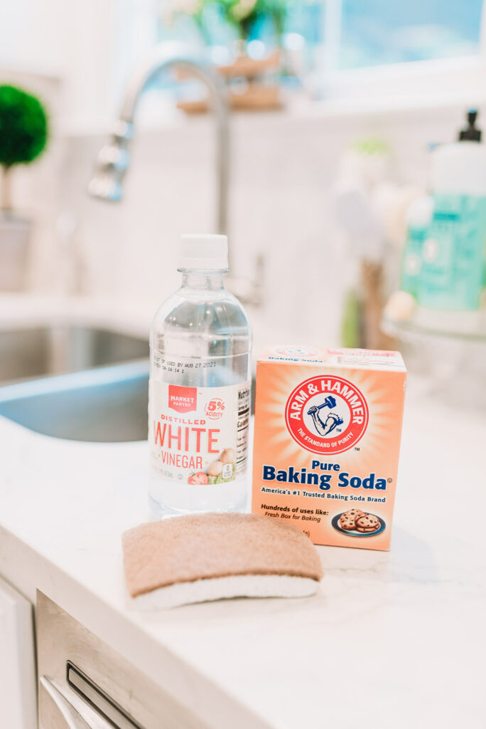 White vinegar baking soda and a walnut scrubber sponge from Grove Collaborative used as a chemical free natural way to clean your oven and stove with Brianna K bitsofbri blog