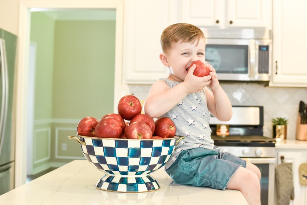 royal blue check Mackenzie Childs large bowl filled with red apples with Landon eating an apple. fourth of July decor ideas. all white kitchen decorated simply for summer with pops of yellow lemons and yellow gingham towels and sunflowers with greenery. three tiered stand decorated for summer with lemons and lemon striped straws and greenery.  White tile vintage lantern backsplash and Ella Cambria quartz countertops with white cabinets and windfresh white walls. Bitsofbri Brianna K summer decor home tour 2019 blog post summer decor inspiration