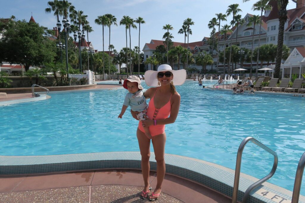 Brianna K and Landon in swimsuits and floppy hats by the pool at Disney's Grand Floridian Resort and Spa Where to stay at Disney World blog post by Brianna K bitsofbri blog