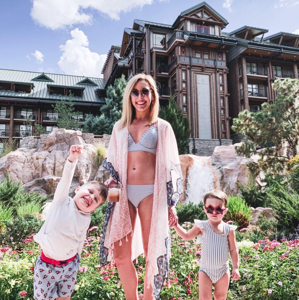 Landon, Presley, and Brianna K by the waterfalls at the pool at Disney's Wilderness Lodge Resort. Where to stay at Disney World blog post by Brianna K bitsofbri blog
