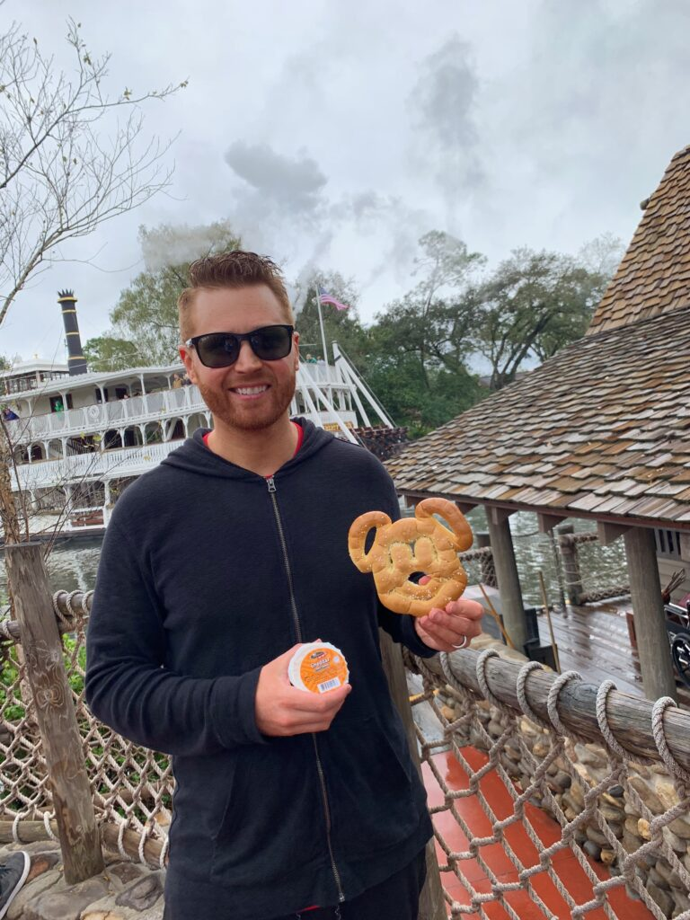 Best snacks you have to try at Walt Disney World | Disney Blog series by Brianna K bits of bri blog  Adam having mickey pretzel and cheese at Walt Disney World