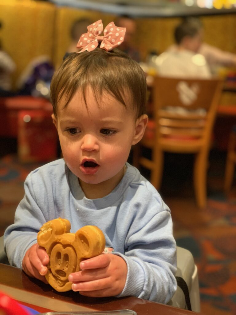 Best snacks you have to try at Walt Disney World | Disney Blog series by Brianna K bits of bri blog  Presley eating a mickey waffle