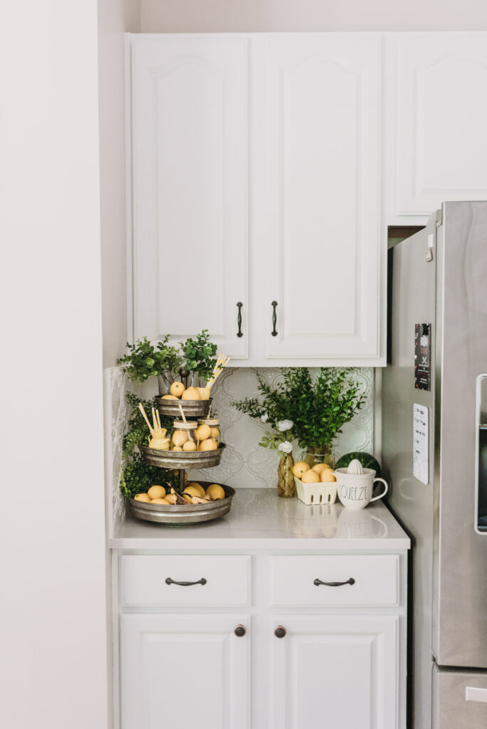 all white kitchen decorated simply for summer with pops of yellow lemons and yellow gingham towels and sunflowers with greenery. three tiered stand decorated for summer with lemons and lemon striped straws and greenery.  White tile vintage lantern backsplash and Ella Cambria quartz countertops with white cabinets and windfresh white walls. Bitsofbri Brianna K summer decor home tour 2019 blog post summer decor inspiration