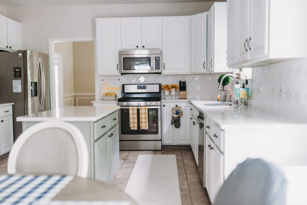 all white kitchen decorated simply for summer with pops of yellow lemons and yellow gingham towels and sunflowers with greenery. White tile vintage lantern backsplash and Ella Cambria quartz countertops with white cabinets and windfresh white walls. Bitsofbri Brianna K summer decor home tour 2019 blog post summer decor inspiration