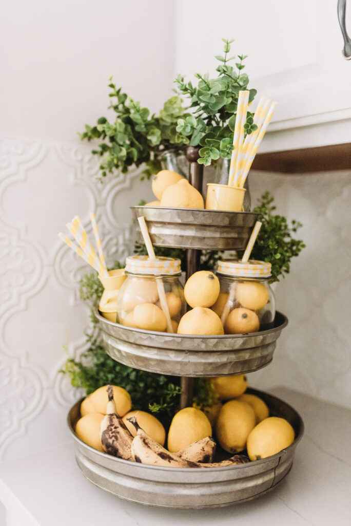 three tiered stand decorated for summer with lemons and lemon striped straws and greenery.  Bitsofbri Brianna K summer decor home tour 2019 blog post summer decor inspiration