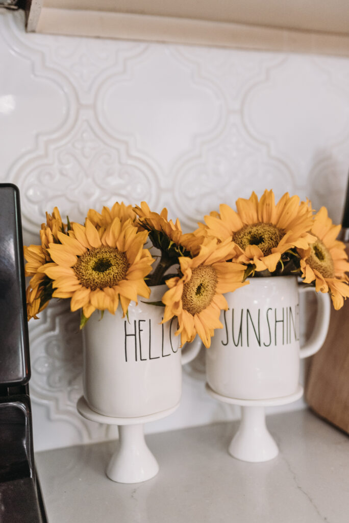 rae dunn hello sunshine cups filled with sunflowers all white kitchen decorated simply for summer with pops of yellow lemons and yellow gingham towels and sunflowers with greenery. three tiered stand decorated for summer with lemons and lemon striped straws and greenery.  White tile vintage lantern backsplash and Ella Cambria quartz countertops with white cabinets and windfresh white walls. Bitsofbri Brianna K summer decor home tour 2019 blog post summer decor inspiration
