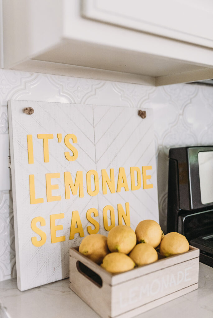 it's lemonade season sign with basket of lemons that say lemonade all white kitchen decorated simply for summer with pops of yellow lemons and yellow gingham towels and sunflowers with greenery. three tiered stand decorated for summer with lemons and lemon striped straws and greenery.  White tile vintage lantern backsplash and Ella Cambria quartz countertops with white cabinets and windfresh white walls. Bitsofbri Brianna K summer decor home tour 2019 blog post summer decor inspiration