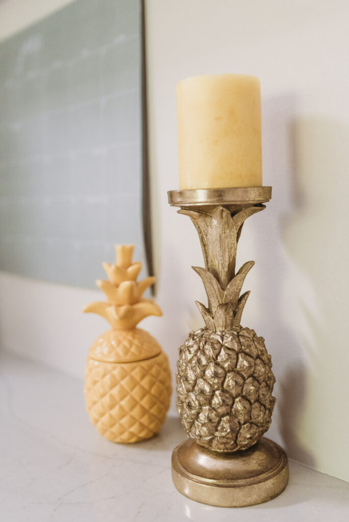 yellow pineapple and gold pineapple candle holder with yellow candle all white kitchen decorated simply for summer with pops of yellow lemons and yellow gingham towels and sunflowers with greenery. three tiered stand decorated for summer with lemons and lemon striped straws and greenery.  White tile vintage lantern backsplash and Ella Cambria quartz countertops with white cabinets and windfresh white walls. Bitsofbri Brianna K summer decor home tour 2019 blog post summer decor inspiration