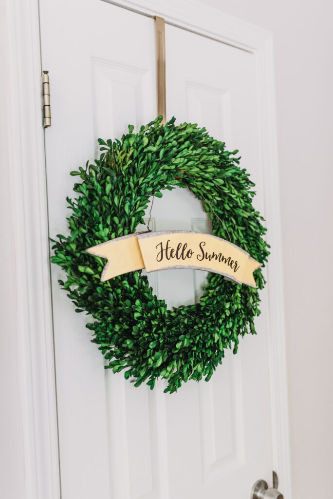 "green boxwood wreath with yellow ""hello summer"" sign hanging on gold wreath door hanger. Bitsofbri Brianna K summer decor home tour 2019 blog post summer decor inspiration"