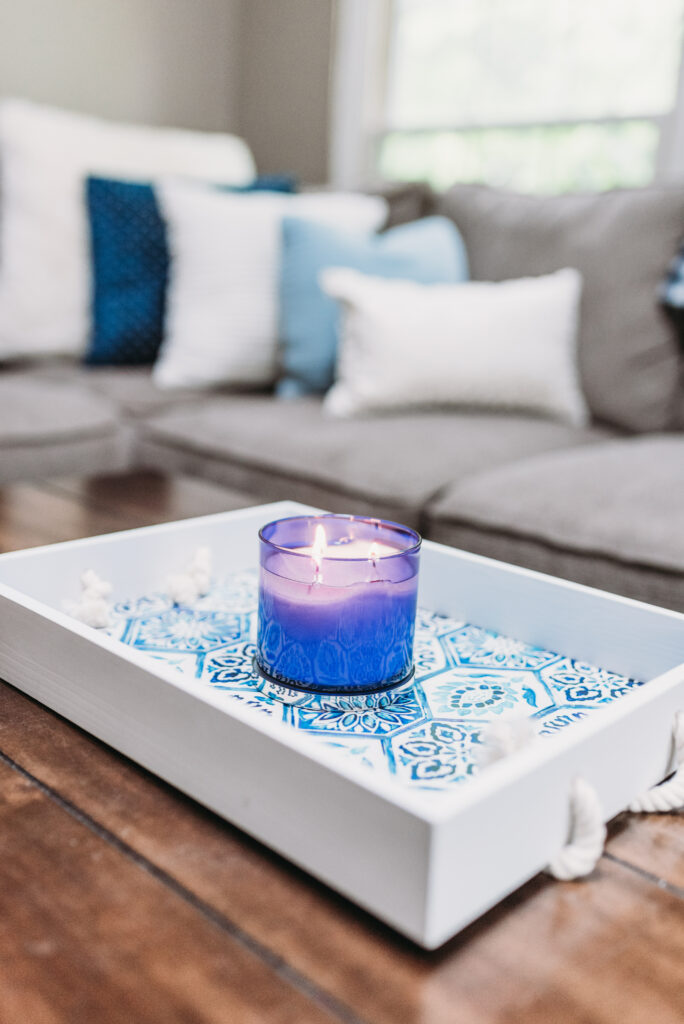 blue and white decorative tray with bright blue candle for summer decor in family room. mantle decor ideas for summer- blue candle holders, gold pineapple, white pineapple, cotton filled vase, large white clock hanging able mantle with family pictures and greenery garland strung across mantle. Bitsofbri Brianna K summer decor home tour 2019 blog post summer decor inspiration