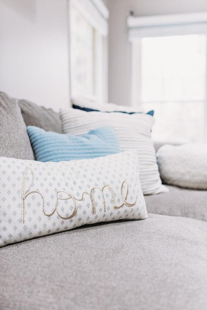 home pillow on couch. Bitsofbri Brianna K summer decor home tour 2019 blog post summer decor inspiration