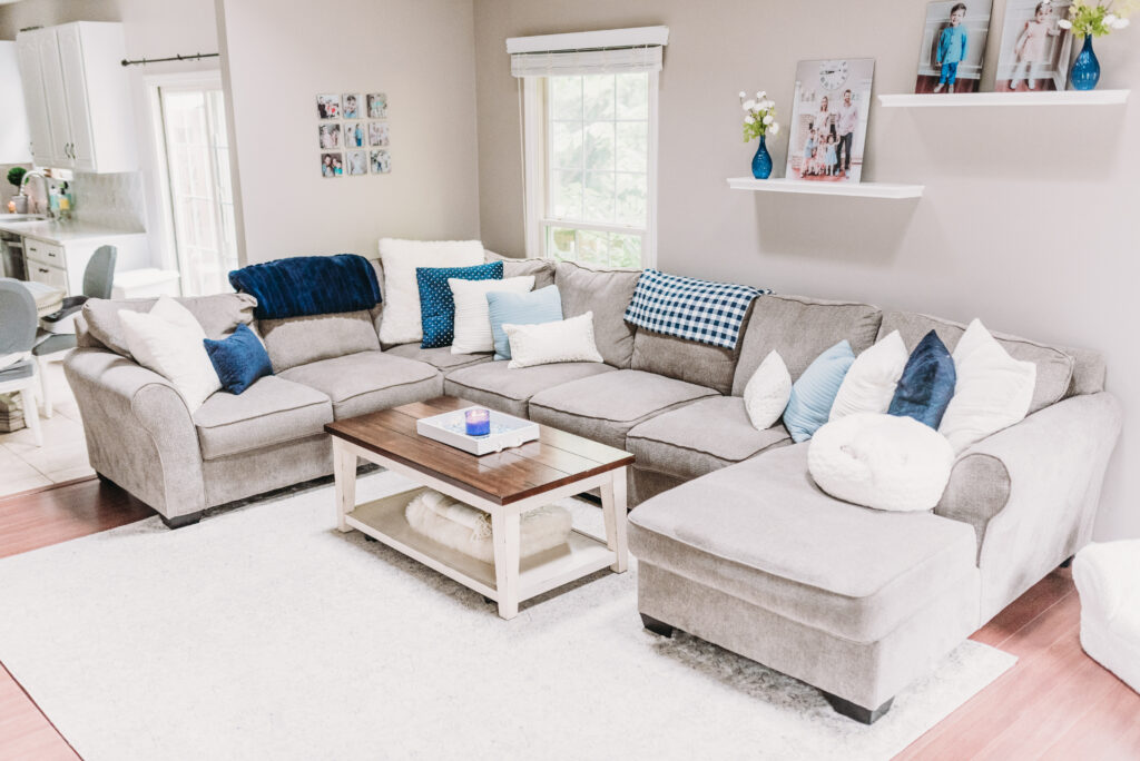 summer decor ideas for family room blue pillows on neutral gray couch with white pillows. mantle decor ideas for summer- blue candle holders, gold pineapple, white pineapple, cotton filled vase, large white clock hanging able mantle with family pictures and greenery garland strung across mantle. Bitsofbri Brianna K summer decor home tour 2019 blog post summer decor inspiration