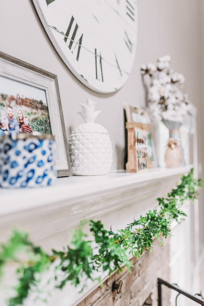 mantle decor ideas for summer- blue candle holders, gold pineapple, white pineapple, cotton filled vase, large white clock hanging able mantle with family pictures and greenery garland strung across mantle. Bitsofbri Brianna K summer decor home tour 2019 blog post summer decor inspiration